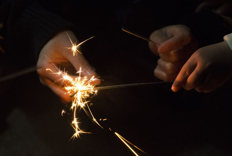Close-up of hands holding sparklers at night