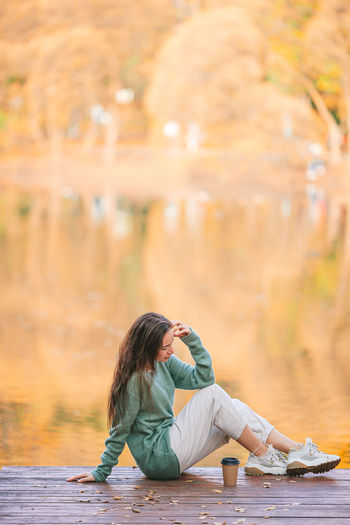 Woman sitting on floor by water