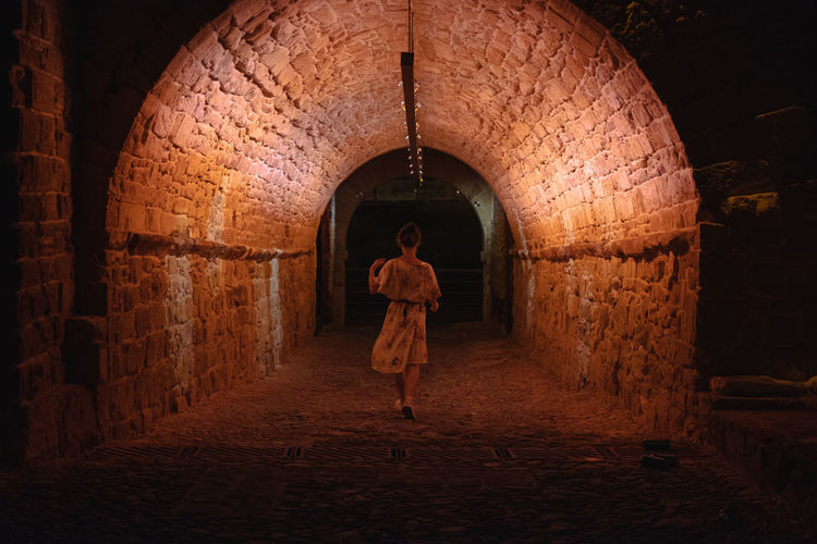 One Person Architecture Arch Rear View Brick Wall - Building Feature Illuminated Brick Wall Dress Beautiful Woman Walking Light And Shadow Tunnel