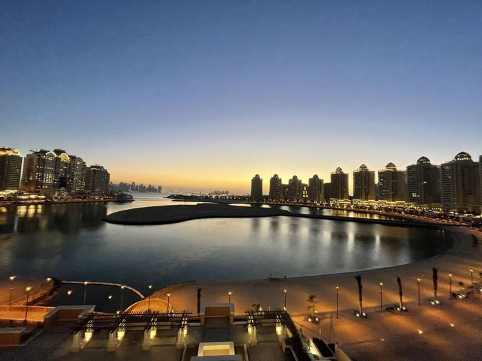 River by illuminated buildings in city against sky during sunset