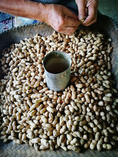 Cropped Hands Of Person Removing Peanuts From Shells