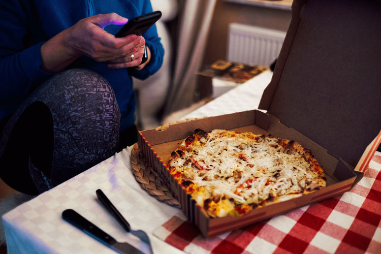 High angle view of man holding pizza on table