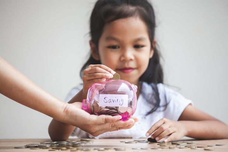 Cropped hand holding piggy bank for girl