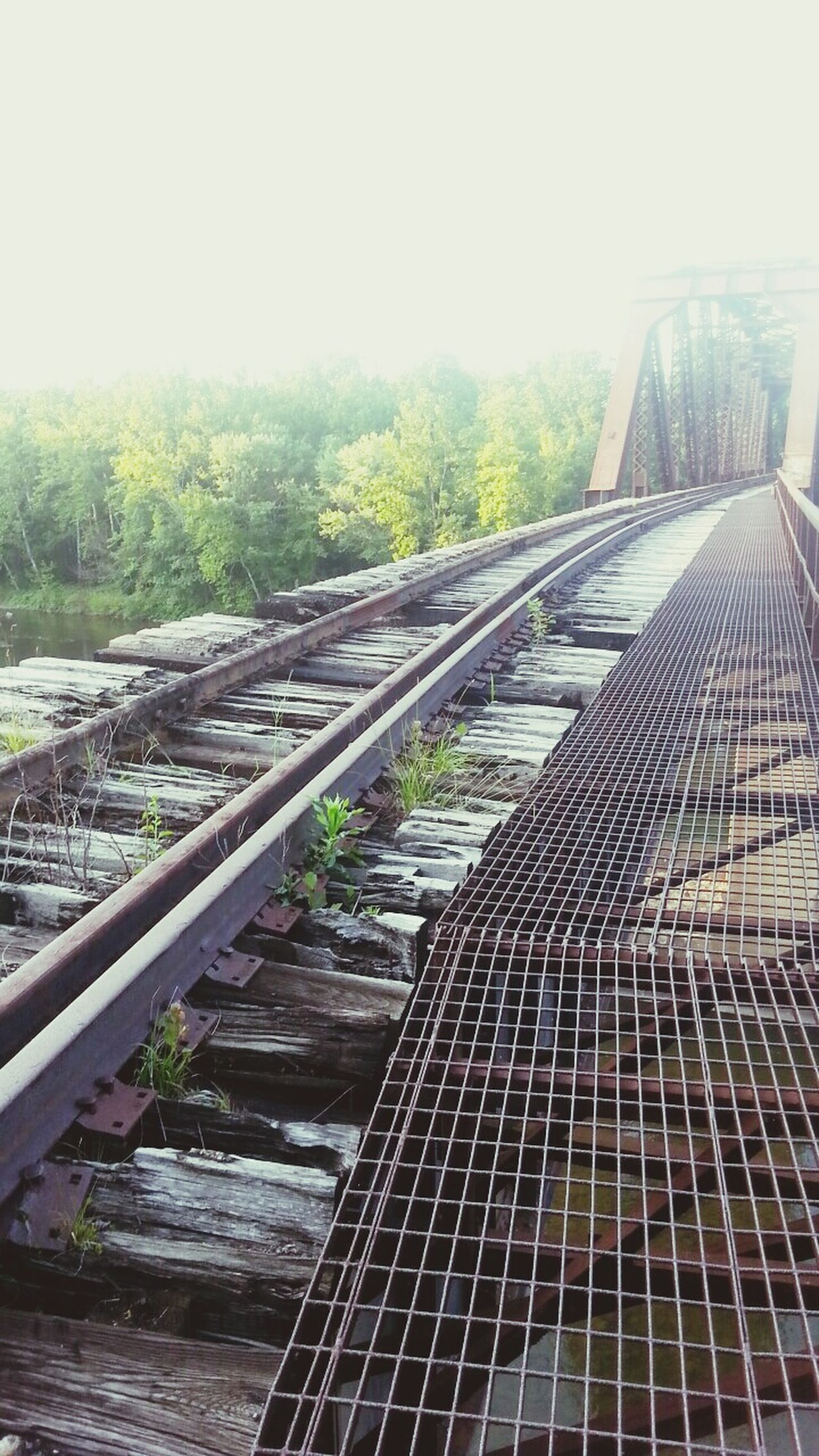 railroad track, rail transportation, transportation, the way forward, diminishing perspective, vanishing point, public transportation, railway track, clear sky, built structure, day, tree, sunlight, metal, architecture, sky, outdoors, no people, high angle view, railroad station