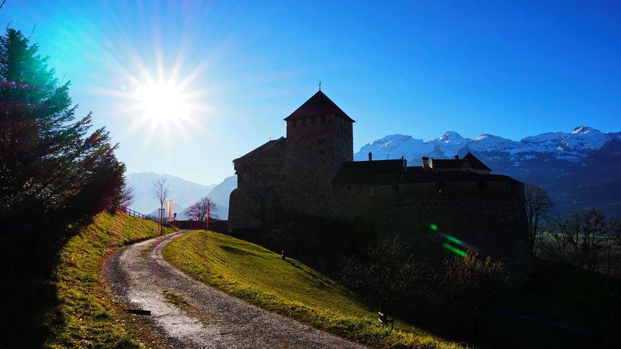 Castle by buildings against clear blue sky