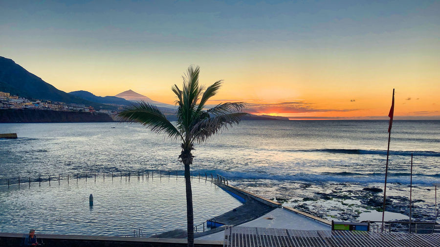Sunset at Punta del Hidalgo, Tenerife Norte, with Teide volcano in the distance Water Sky Sea Sunset Palm Tree Swimming Pool