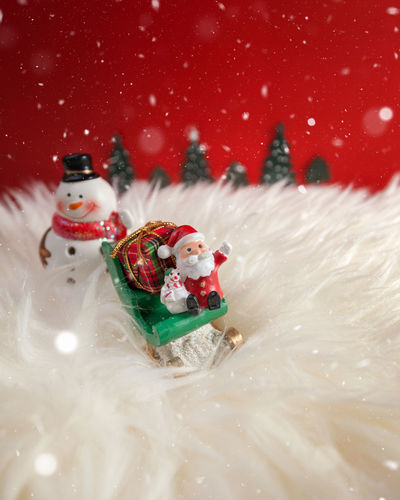 Close-Up Of Christmas Ornaments Against Red Background