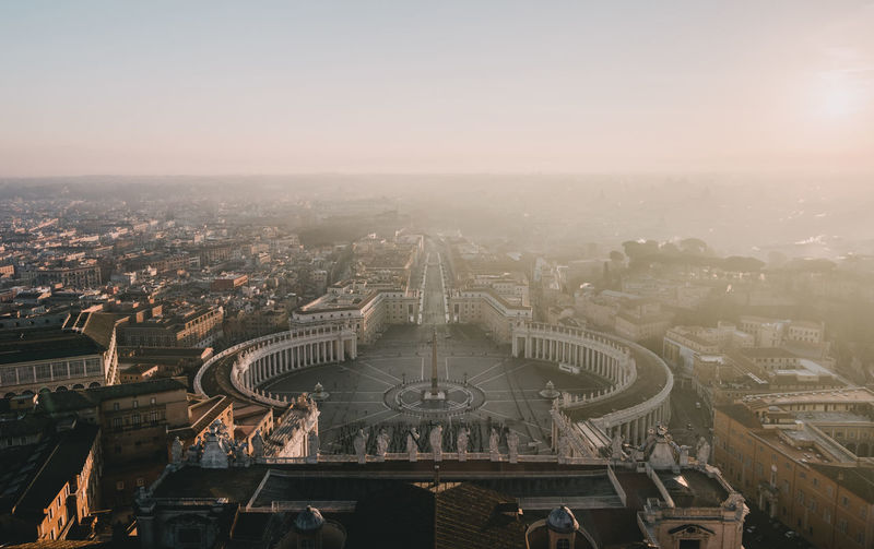 High angle view of st peter basilica in city against sky during sunset