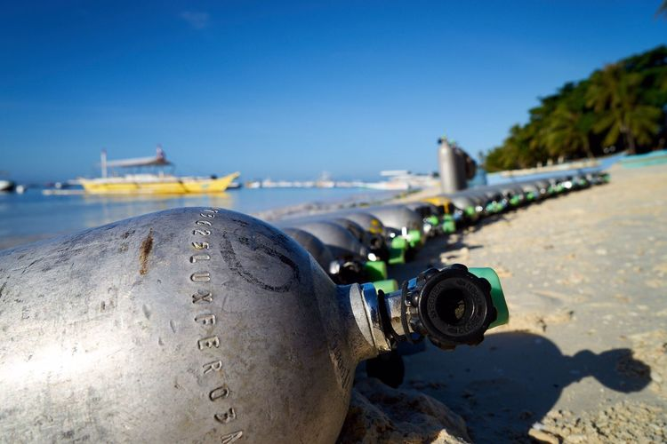 Close-up of scuba diving cylinders on beach