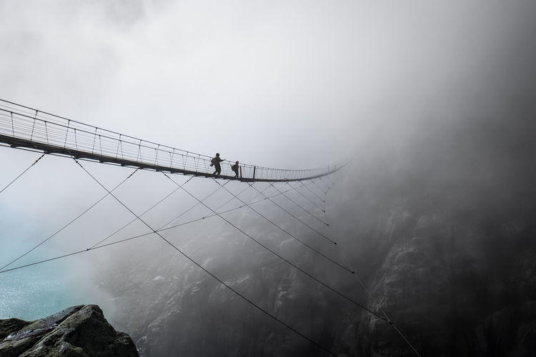 Low angle view of footbridge during foggy weather against sky