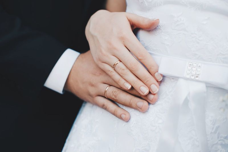Midsection of bride and groom wearing wedding rings