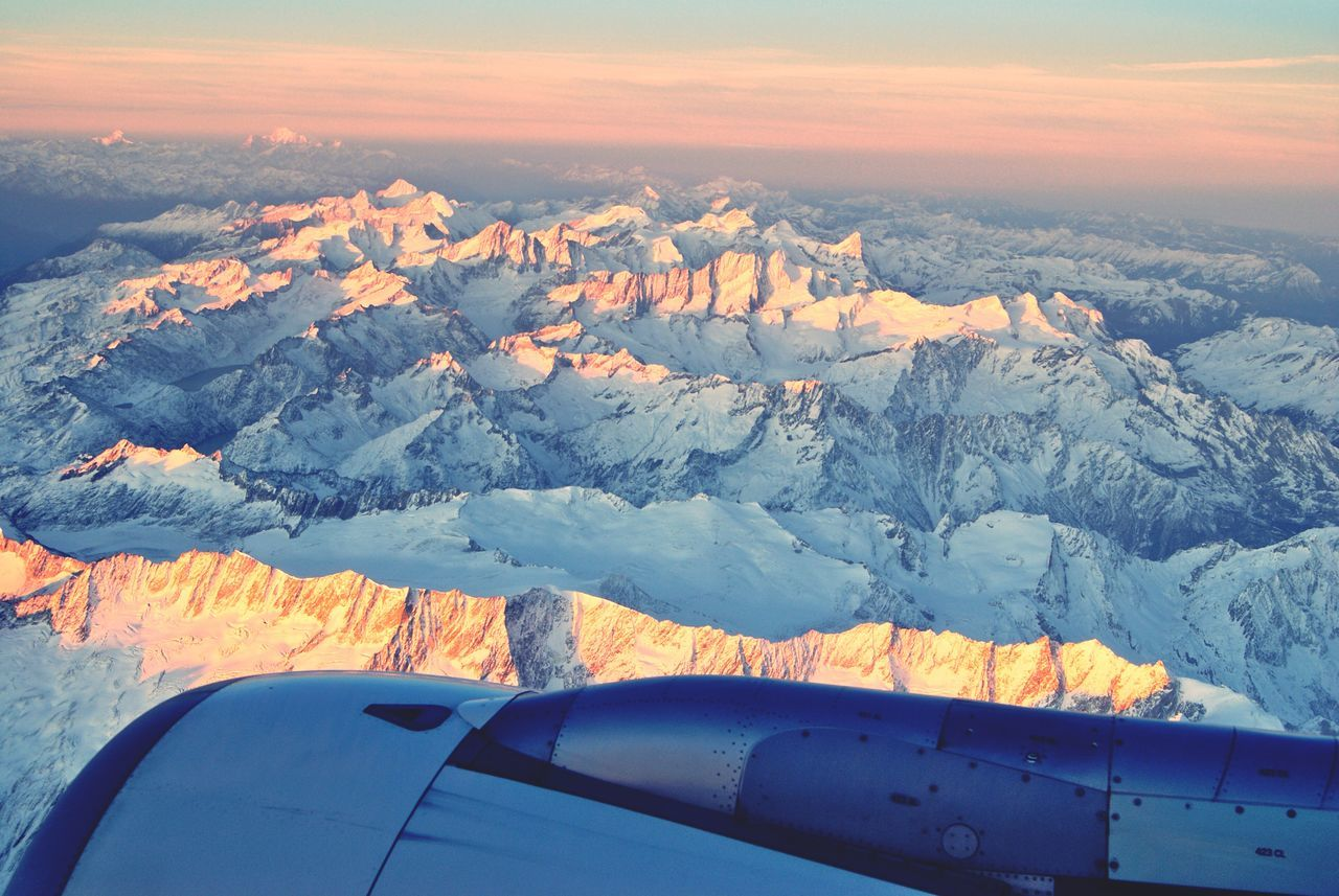 Cropped Image Of Airplane Over Snowcapped Mountains