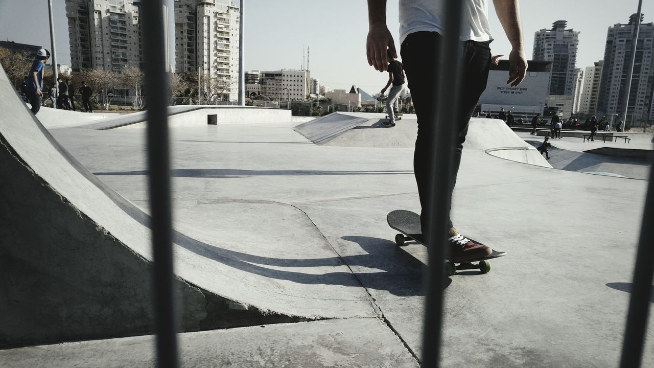 low section, city, architecture, human leg, real people, leisure activity, shadow, sport, sunlight, outdoors, men, jumping, challenge, building exterior, one person, day, skateboard park, sportsman, people