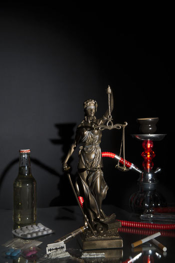 Legal and illegal intoxicants - Justitia statue in the midst of intoxicants in front of black background with copy space Addiction Advice Cigarettes Crime Drugs Intoxicant Pills Procurement Crime Addiction Alcohol Black Background Cocaine Concept Consumption  Extasy Hookah Illegal Interdiction Justice Law Legal Penalty Prohibited Punishment Statue Youth Protection