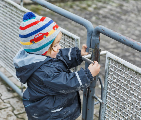 Side View Of Girl Holding Metal Gate During Winter