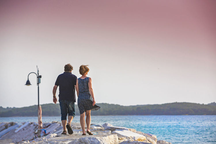 Rear view of couple walking on pier by sea against clear sky