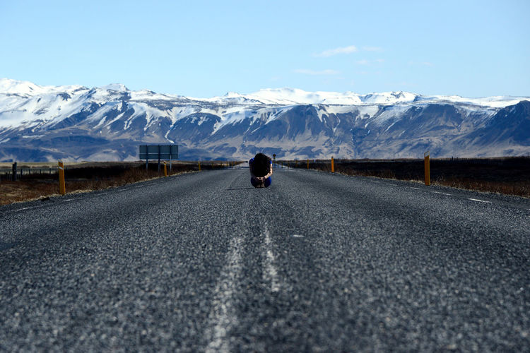 The girl sit on the road in Island. Clasped Hands Road Sitting Woman Adult Beauty In Nature Cold Temperature Embrace Female Girl Highway Mountain Mountain Range Nature One Person Outdoors People Road Scenics Sky Snow Snowcapped Mountain The Way Forward Tranquil Scene Winter Stories From The City