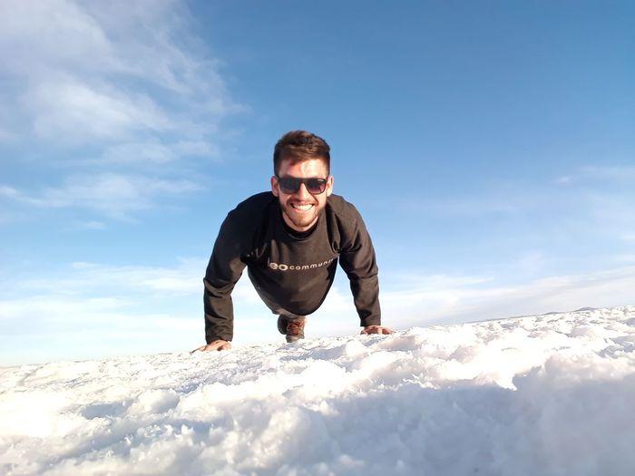 Portrait of man doing push-ups on snow against sky