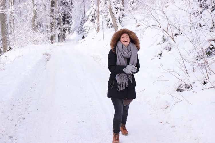 Cheerful Young Woman Wearing Warm Clothing Standing In Snow