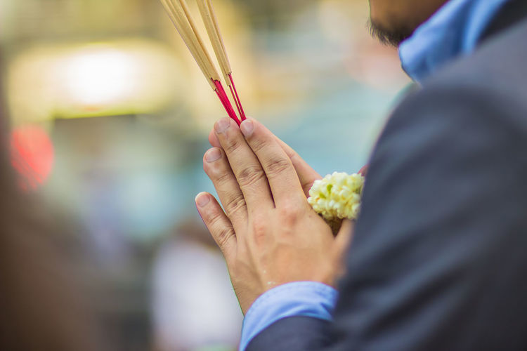 Cropped Hands Of Man Holding Incense Sticks With Floral Garland In Temple