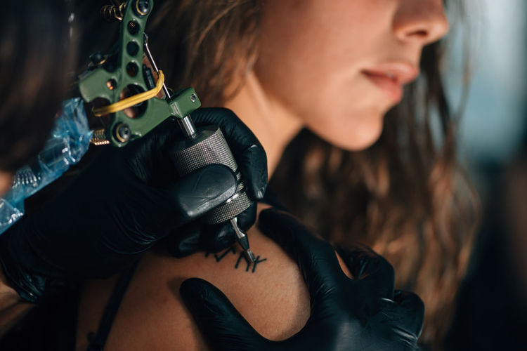Tattoo artist working with cool girl Cool Lifestyle Tattoo Artist Tattoo Parlor Tattooed Tattooing Woman Beautiful Woman Close-up Girl Gloves Hand Inked Inked Girl Lifestyles People Pretty Girl Tattoo Tattoo Girl Tattoo Gun Tattooist Tattoomodels Toned Image Urban Young Adult