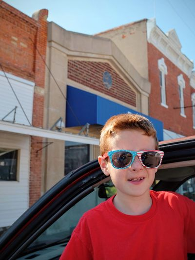 Portrait of boy wearing sunglasses while standing by car in city