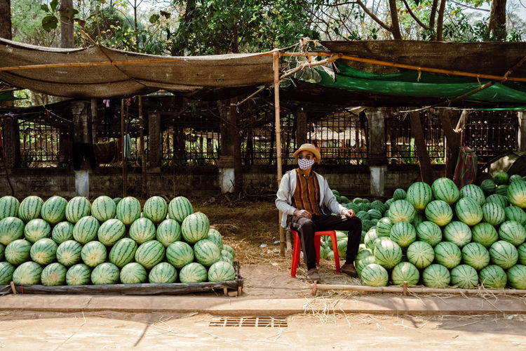 Full length of man sitting at market stall
