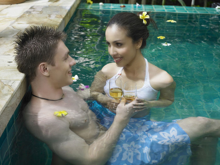 High Angle View Of Couple Having Drink In Swimming Pool