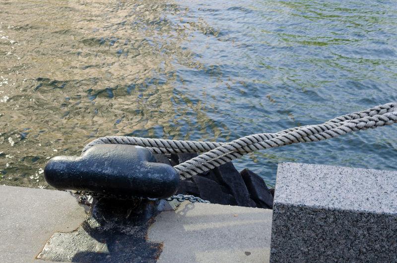 Close-up of ropes at bollard against water