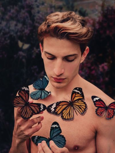 Shirtless man with colorful butterflies stickers