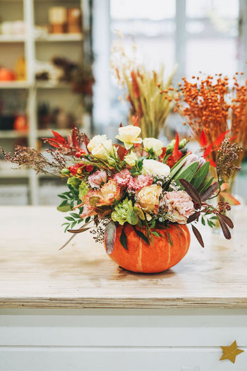 Diy autumn flower arrangement bouquet in pumpkin at floristry studio