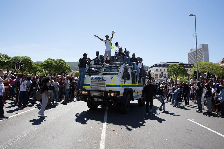 A RG-12 Nyala South African Police Vehicle leaves Parliament with Students from the Fees Must Fall movement ontop of the vehicle. 28th October 2016 Cape Town Feesmustfall Large Group Of People Police Force Protests South Africa The Photojournalist - 2017 EyeEm Awards