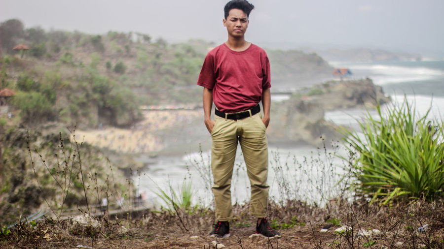 Portrait of young man standing on land