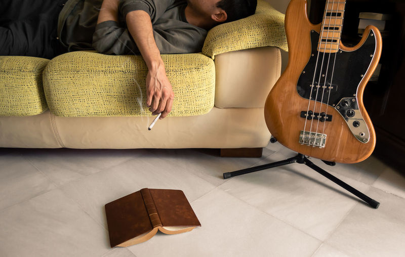 Midsection of man smoking while lying on sofa at home