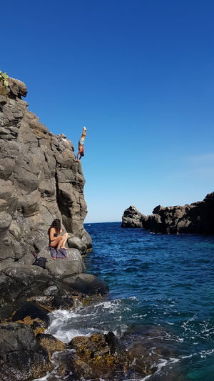 People on rock formation by sea against clear blue sky