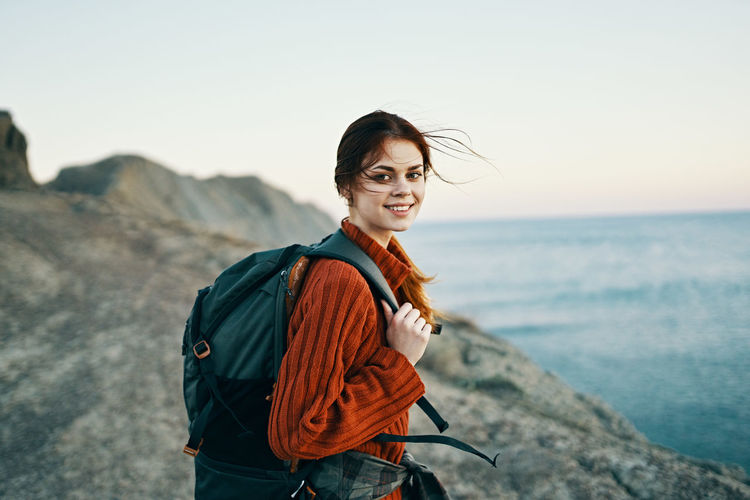 Portrait of smiling young woman standing on sea shore against sky