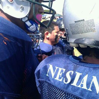 my nephew in the huddle getting ready to play some football..