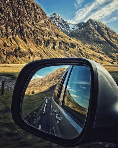 Reflection of mountains on side-view mirror