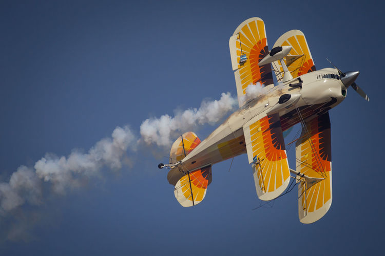 Low angle view of biplane flying against sky