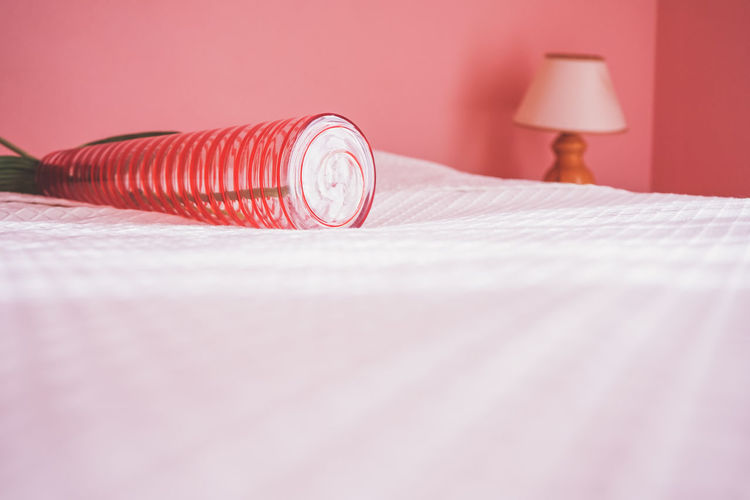 Close-up of electric lamp on bed at home