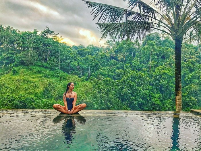 Water One Person Real People Tree Plant Leisure Activity Lifestyles Nature Green Color Women Sitting Swimming Pool Sky Day Waterfront Young Adult Full Length Outdoors Cloud - Sky