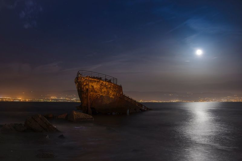 Abandoned Ship In Sea Against Sky At Night