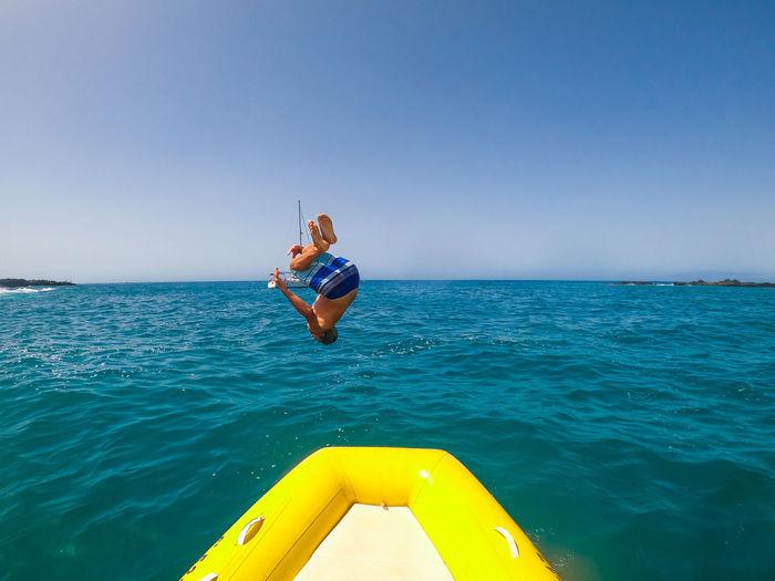 Full length of boy jumping in sea against sky