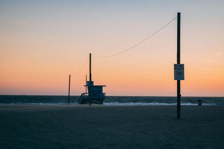 Lifeguard hut on beach against sky during sunset
