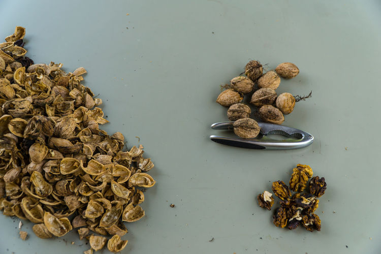 Directly above shot of walnuts with nutcracker on table