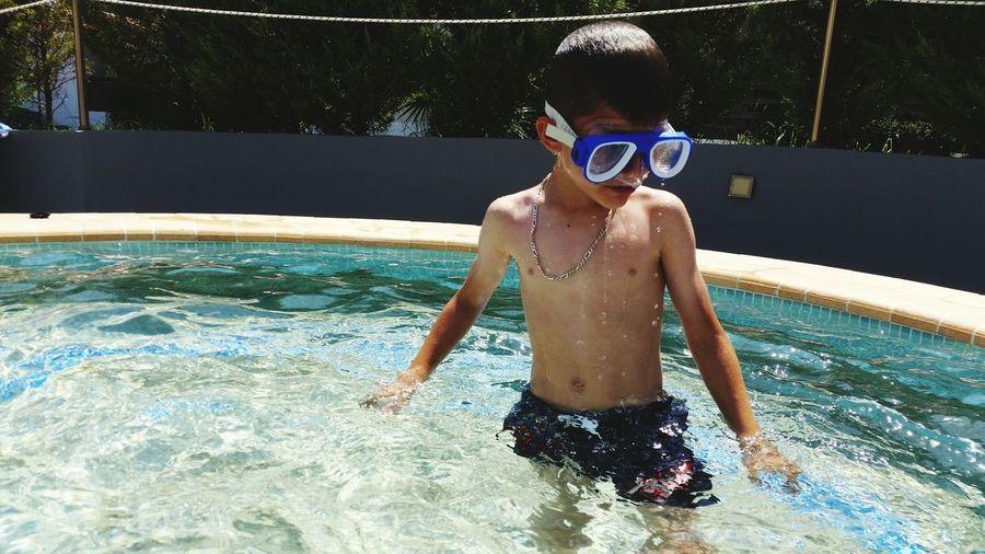 Shirtless boy standing in swimming pool