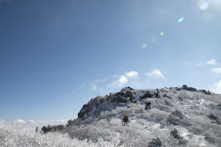 Low angle view of people hiking snow covered mountain