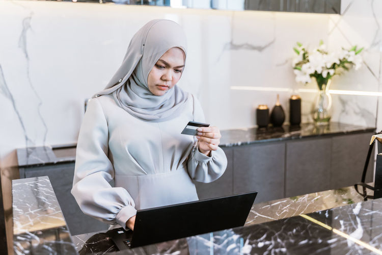 Mid adult woman wearing hijab doing online shopping over laptop while standing at home