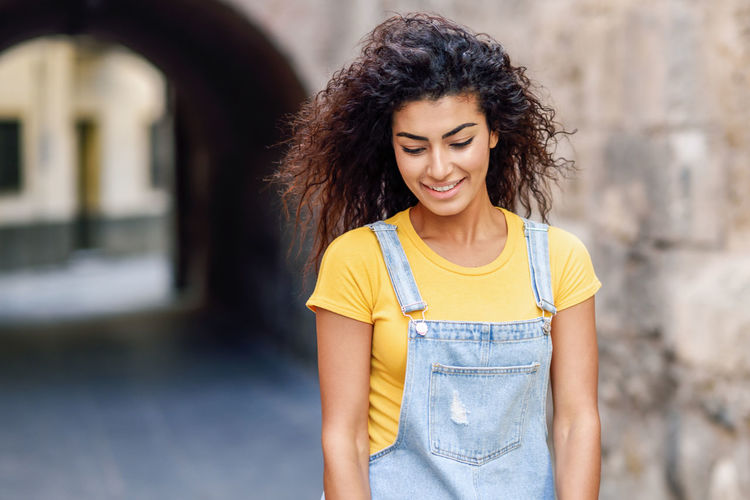 Young Woman Smiling While Standing On Footpath