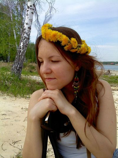 Young Woman Wearing Flower Wreath In Her Hair While Sitting At Beach